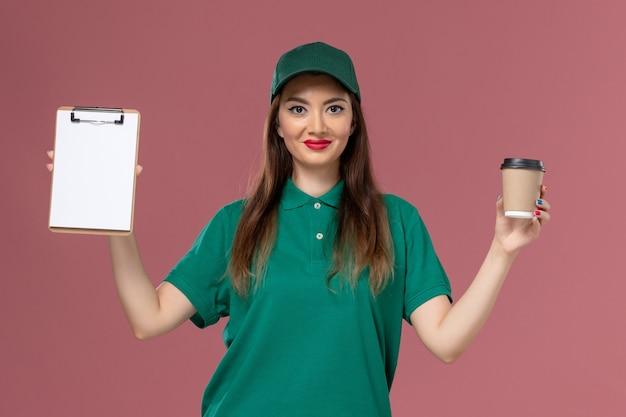 Widok z przodu kurierka w zielonym mundurze i pelerynie trzymającej dostawę filiżankę kawy i notatnik na różowej ścianie usługi służbowe jednolite firma kurierska