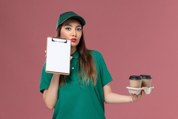 Widok z przodu kurierka w zielonym mundurze i pelerynie trzymającej dostawy filiżanek kawy i notatnika na różowej ścianie usługa praca jednolita dostawa