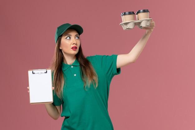 Widok z przodu kurierka w zielonym mundurze i pelerynie trzymającej notatnik i dostawy filiżanek na różowym biurku jednolita dostawa