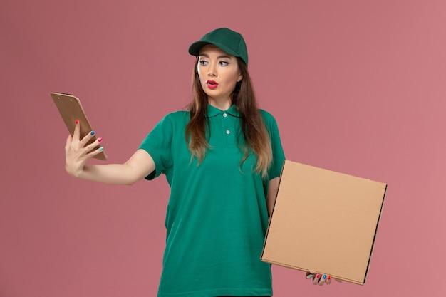 Widok z przodu kurierka w zielonym mundurze trzyma pudełko z jedzeniem i notatnik na różowej ścianie usługa firmy jednolita dostawa praca