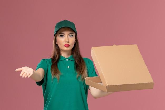 Widok z przodu kurierka w zielonym mundurze, trzymająca pudełko z dostawą żywności na różowej ścianie, jednolita usługa pracy firmy