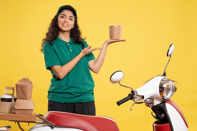 Widok z przodu kurierka w zielonym mundurze z deserem na żółtym tle kolor pracy praca dostawa kobieta pracownik obsługi jedzenie