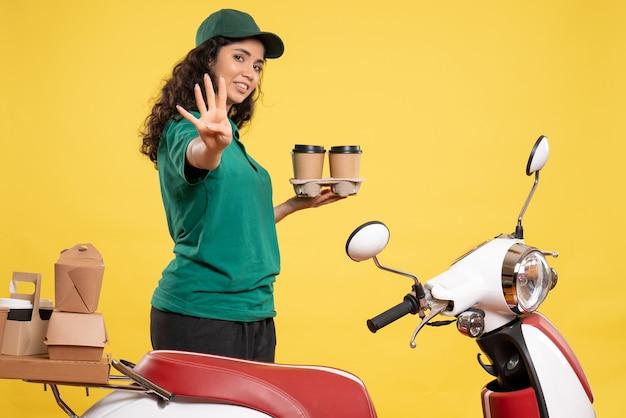 Widok z przodu kurierka w zielonym mundurze z kawą na żółtym tle kolor praca dostawa praca jedzenie kobieta pracownik obsługi