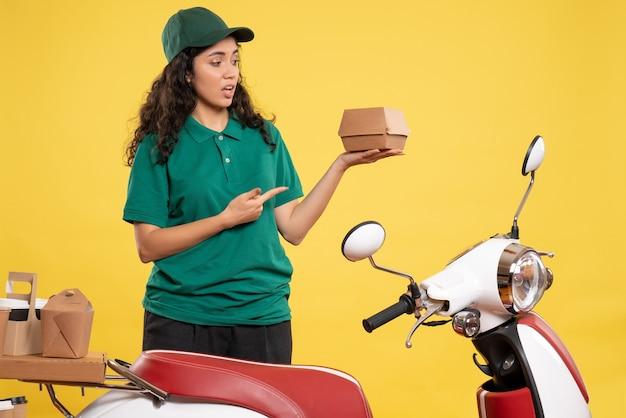 Widok z przodu kurierka w zielonym mundurze z małym opakowaniem żywności na żółtym tle praca kolor praca dostawa pracownik usług gastronomicznych