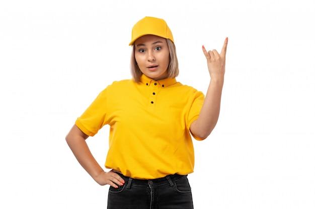 Widok z przodu kurierka w żółtej koszuli, żółtej czapce i czarnych dżinsach, pozująca w stylu rocker na białym tle