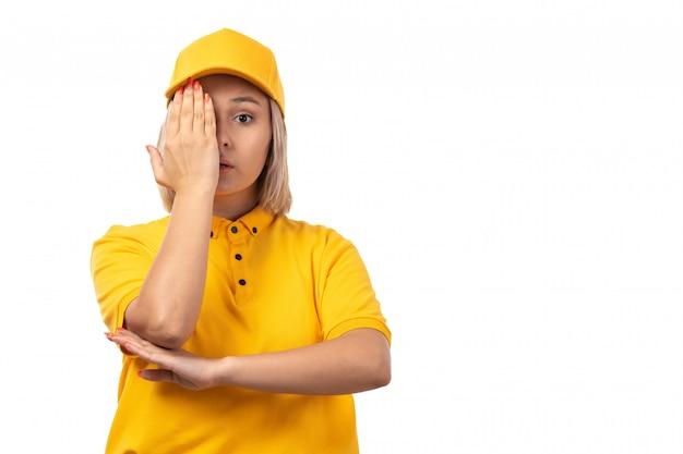 Widok z przodu kurierka w żółtej koszuli, żółtej czapce i czarnych dżinsach, pozująca zakrywająca jedno oko na białym
