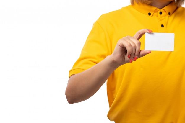Widok z przodu kurierka w żółtej koszuli, żółtej czapce i czarnych dżinsach, trzymając białą kartkę na białym tle