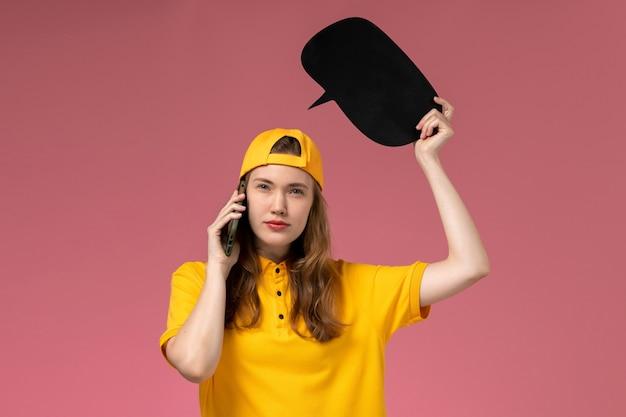 Widok z przodu kurierka w żółtym mundurze i pelerynie, trzymająca czarny znak i rozmawiająca przez telefon na różowej ścianie mundur dostawy pracownika firmy