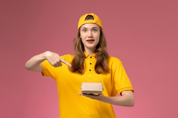 Widok z przodu kurierka w żółtym mundurze i pelerynie trzymająca dostawę paczki żywności na różowej ścianie mundur dostawy usług pracownik firmy