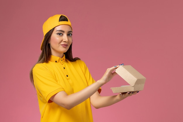 Widok z przodu kurierka w żółtym mundurze i pelerynie trzymająca małą paczkę z dostawą żywności i otwierająca ją na różowej ścianie jednolita praca firmy kurierskiej