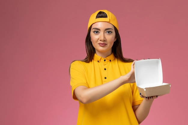 Widok z przodu kurierka w żółtym mundurze i pelerynie trzymająca małą paczkę z dostawą żywności i otwierająca ją na różowej ścianie pracownik firmy świadczącej usługi w mundurze