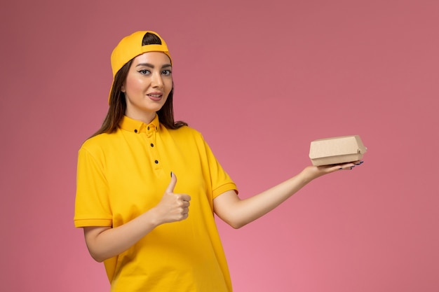 Widok z przodu kurierka w żółtym mundurze i pelerynie trzymająca małą paczkę z dostawą żywności na różowej ścianie jednolita usługa dostawy pracy pracownika