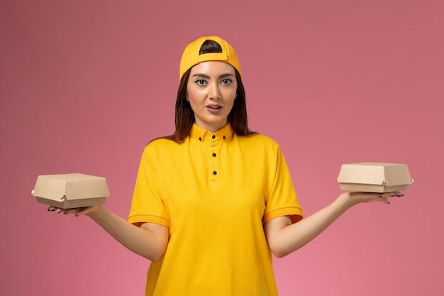 Widok z przodu kurierka w żółtym mundurze i pelerynie trzymająca małe paczki z dostawą żywności na jasnoróżowej ścianie