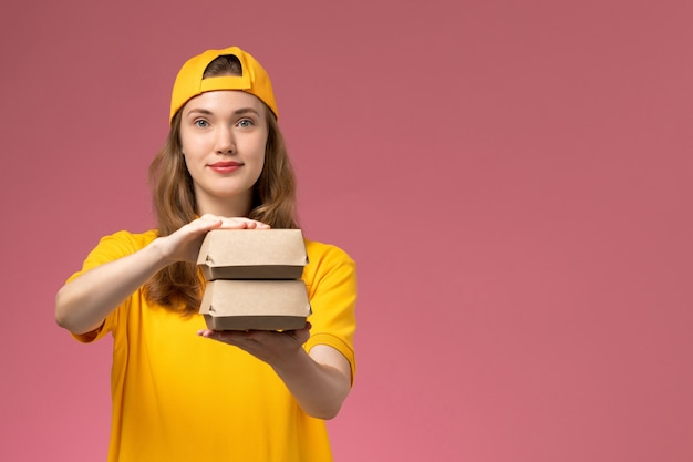 Widok z przodu kurierka w żółtym mundurze i pelerynie trzymająca małe paczki żywnościowe na różowej ścianie mundur dostawy pracownika usługowego
