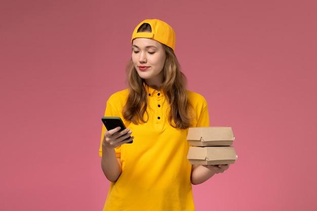 Widok z przodu kurierka w żółtym mundurze i pelerynie trzymająca telefon z opakowaniami żywności na różowej ścianie firma świadcząca usługi w mundurze pracy