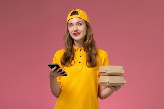 Widok z przodu kurierka w żółtym mundurze i pelerynie trzymająca telefon z paczkami żywności uśmiechnięta na różowej ścianie mundur dostawy usług firmy