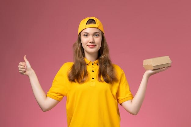 Widok z przodu kurierka w żółtym mundurze i pelerynie trzymającej dostawę paczki żywnościowej na różowej ścianie