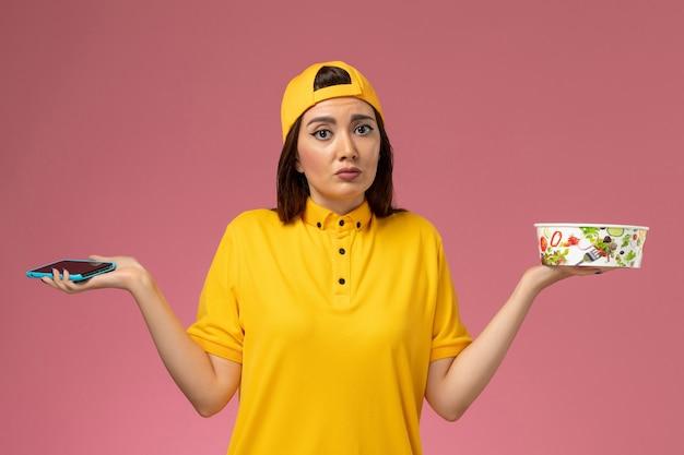 Widok z przodu kurierka w żółtym mundurze i pelerynie trzymającej miskę dostawy i smartfona na jasnoróżowej ścianie
