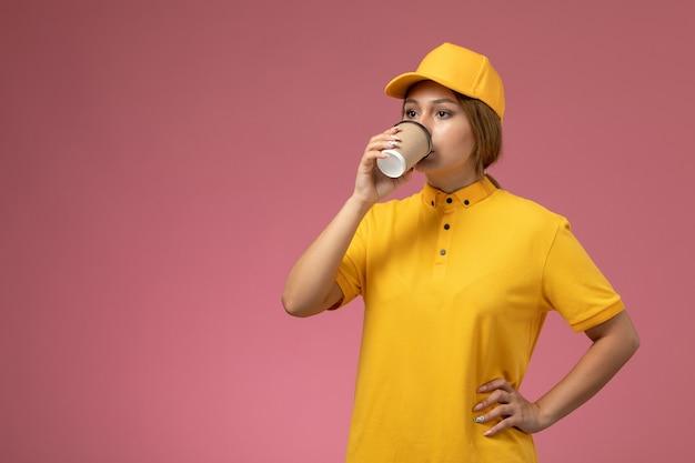 Widok z przodu kurierka w żółtym mundurze żółta peleryna pije kawę na różowym biurku jednolita dostawa kobiet w kolorze