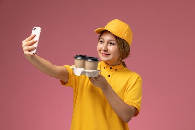 Widok z przodu kurierka w żółtym mundurze żółtej pelerynie trzymającej filiżanki kawy biorąc selfie na różowym tle jednolity kolor pracy dostawy