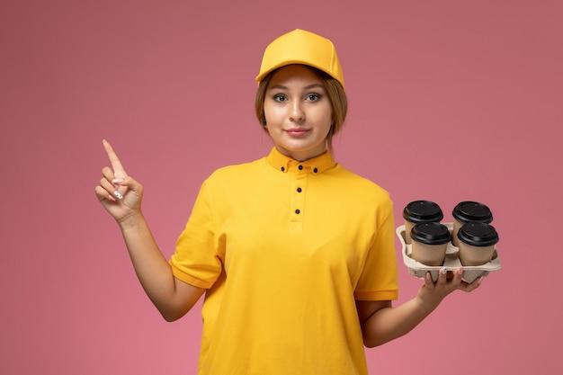 Widok z przodu kurierka w żółtym mundurze żółtej pelerynie trzymającej plastikowe kubki do kawy na różowym tle jednolita dostawa pracy kolor pracy