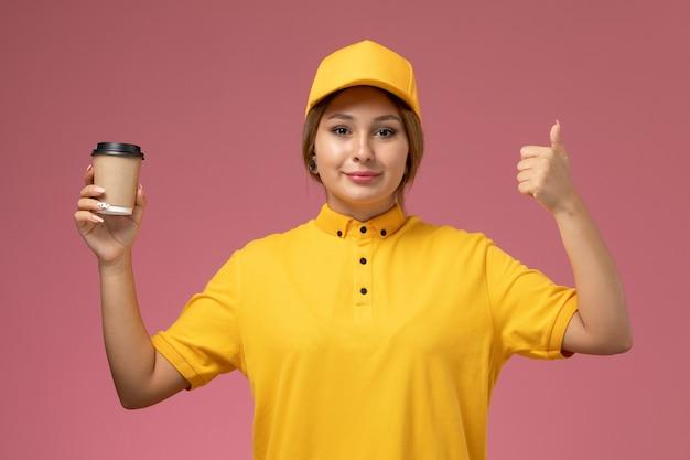 Widok z przodu kurierka w żółtym mundurze żółtej pelerynie trzymającej plastikowy kubek na różowym tle jednolita praca dostawy