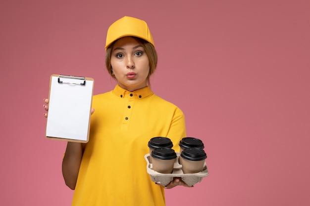 Widok z przodu kurierka w żółtym mundurze żółtej peleryny trzymającej filiżanki kawy i biały notatnik na różowym tle jednolita dostawa pracy kolor pracy