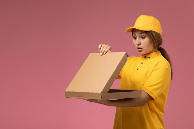 Widok z przodu kurierka w żółtym mundurze żółtej peleryny trzymającej i otwierającej pudełko z jedzeniem na różowym biurku jednolita dostawa kobiecego koloru