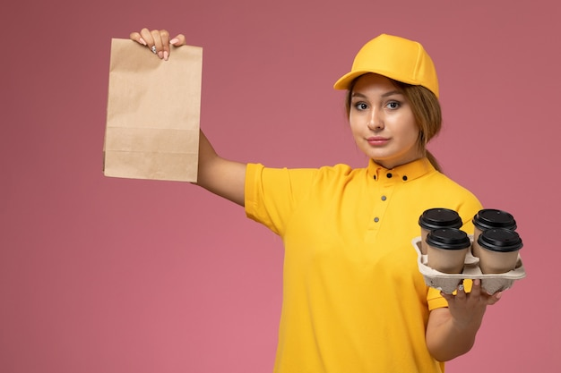 Widok z przodu kurierka w żółtym mundurze żółtej peleryny trzymającej opakowanie żywności z plastikowymi filiżankami do kawy na różowym tle jednolita dostawa pracy kolor pracy