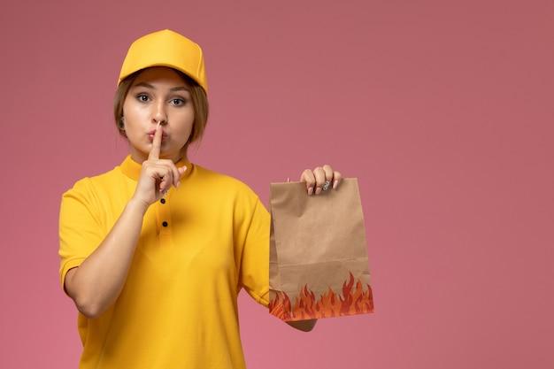 Widok z przodu kurierka w żółtym mundurze żółtej peleryny trzymającej pakiet żywności ze znakiem ciszy na różowym biurku jednolita dostawa pracy kolor pracy