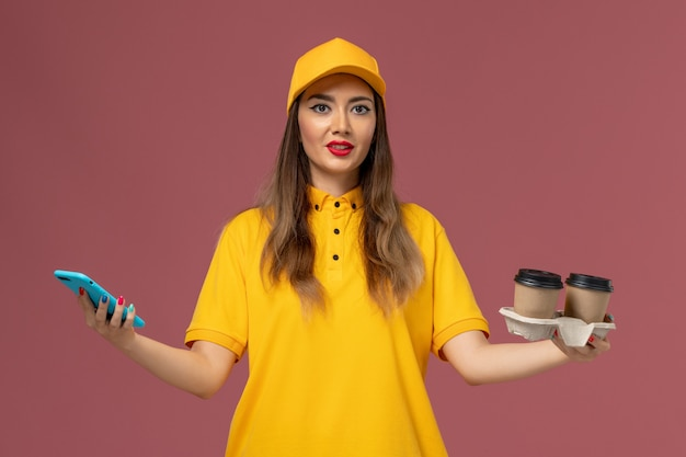 Widok z przodu kurierki w żółtym mundurze i czapce trzymającej dostawy filiżanek i smartfona na różowej ścianie