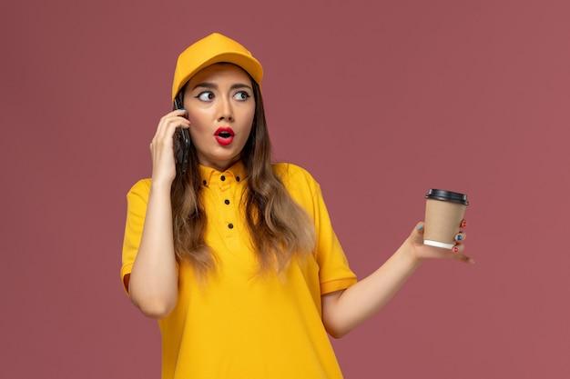Widok z przodu kurierki w żółtym mundurze i czapce trzymającej filiżankę kawy dostawy i rozmawiającej przez telefon na różowej ścianie