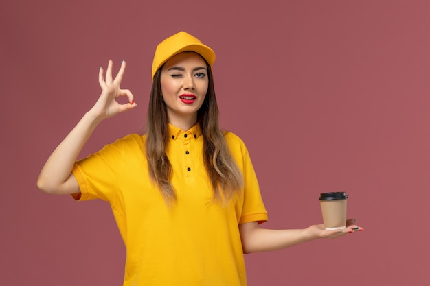 Widok z przodu kurierki w żółtym mundurze i czapce trzymającej filiżankę kawy dostawy na różowej ścianie