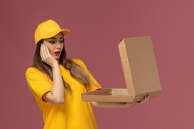 Widok z przodu kurierki w żółtym mundurze i czapce trzymającej otwarte pudełko z jedzeniem na jasnoróżowej ścianie