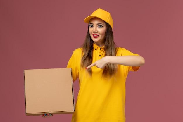 Widok z przodu kurierki w żółtym mundurze i czapce trzymającej pudełko z jedzeniem na jasnoróżowej ścianie