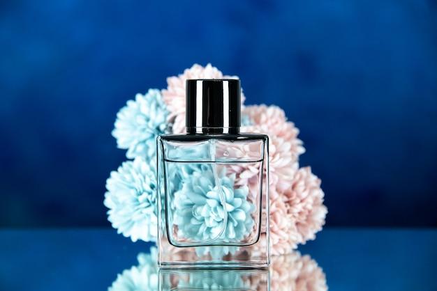 Widok z przodu kwiatów butelek perfum na ciemnoniebieskim rozmytym tle