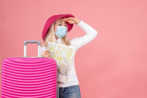 Widok z przodu ładna blondynka kobieta stojąca w pobliżu walizki trzymając obserwację mapy