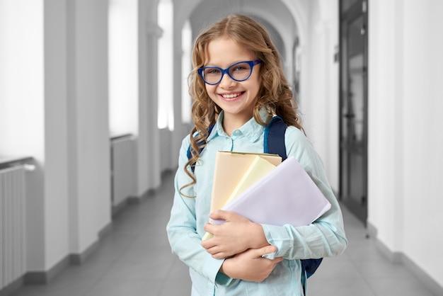 Widok z przodu ładna blondynka uczennice na sobie niebieską koszulę i okulary, trzymając wiele kolorowych notatek i książek.