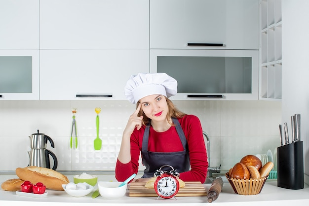Widok z przodu ładna dziewczyna w kapeluszu kucharza i fartuchu stojąca w kuchni