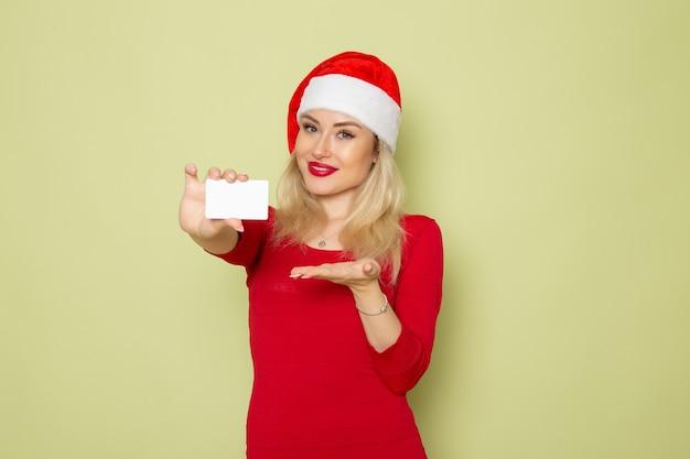 Widok z przodu ładna kobieta trzyma kartę bankową na zielonej ścianie kolor śniegu emocje wakacje nowy rok
