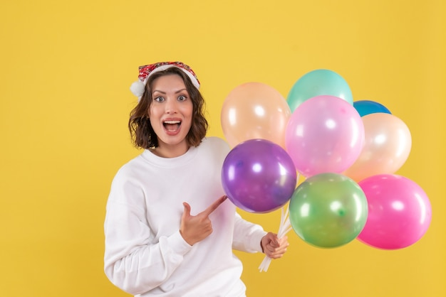 Widok z przodu ładna kobieta trzyma kolorowe balony na żółto