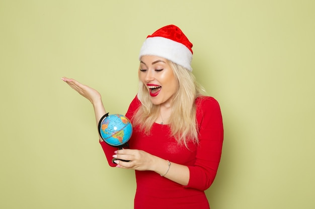 Widok z przodu ładna kobieta trzyma małą kulę ziemską na zielonej ścianie wakacje boże narodzenie