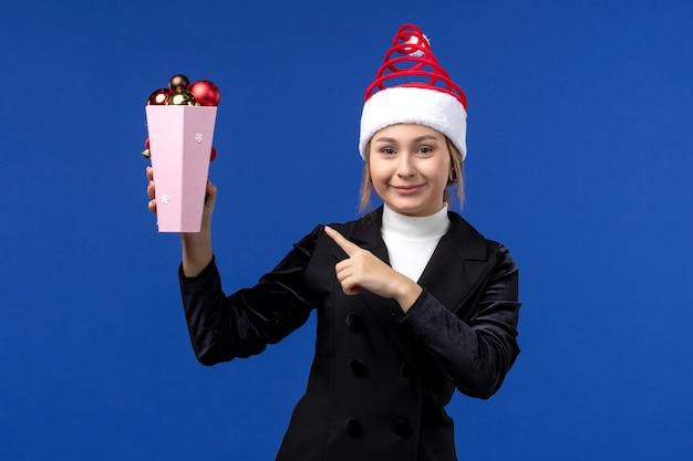 Widok z przodu ładna kobieta trzyma plastikowe zabawki choinkowe na niebieskiej ścianie niebieski nowy rok wakacje