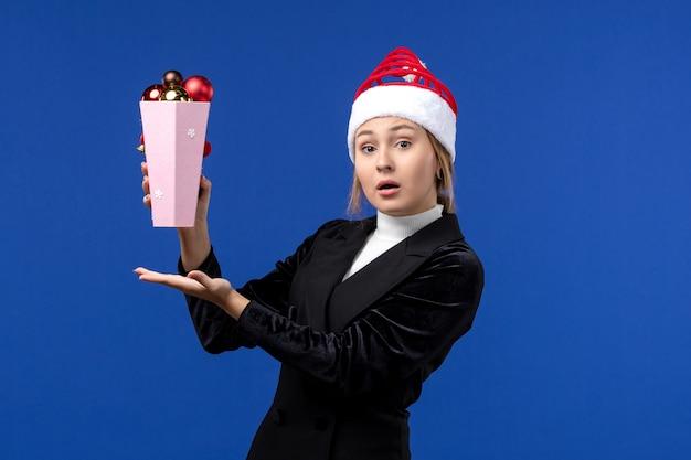 Widok z przodu ładna kobieta trzyma plastikowe zabawki choinkowe na niebieskiej ścianie niebieskie święta nowego roku