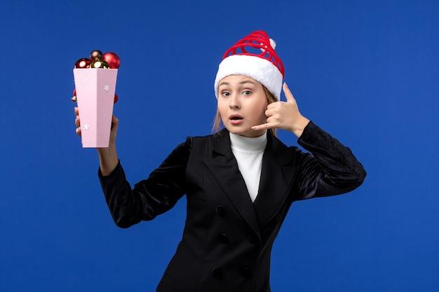 Widok z przodu ładna kobieta trzyma plastikowe zabawki choinkowe na niebieskiej ścianie święta nowego roku na niebiesko