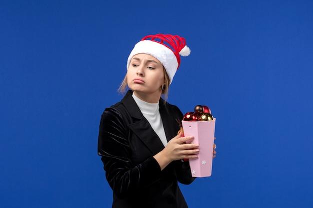 Widok z przodu ładna kobieta trzyma plastikowe zabawki drzewa na niebieskiej podłodze niebieskie wakacje nowy rok