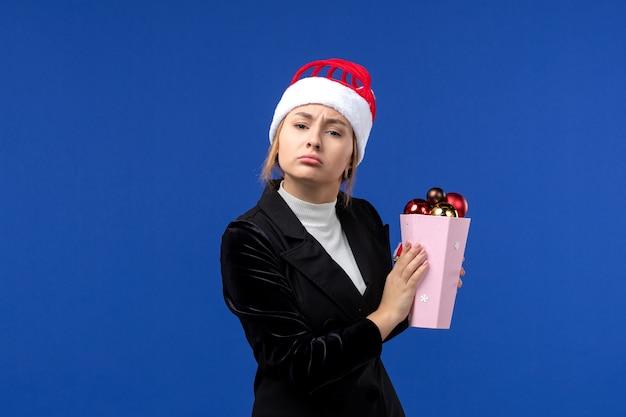 Widok z przodu ładna kobieta trzyma plastikowe zabawki drzewa na niebieskiej ścianie niebieskie wakacje nowy rok