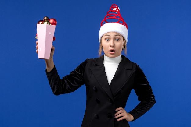 Widok z przodu ładna kobieta trzyma plastikowe zabawki drzewa na niebieskiej ścianie nowy rok wakacje niebieski