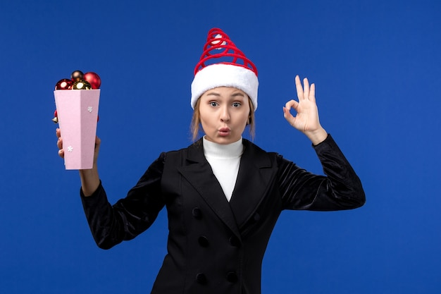 Widok z przodu ładna kobieta trzyma plastikowe zabawki drzewa na niebieskim biurku nowy rok wakacje niebieski