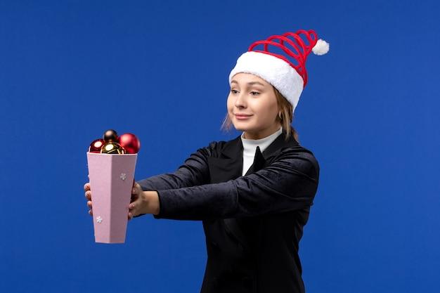 Widok z przodu ładna kobieta trzyma plastikowe zabawki drzewa na niebieskim biurku wakacje nowy rok